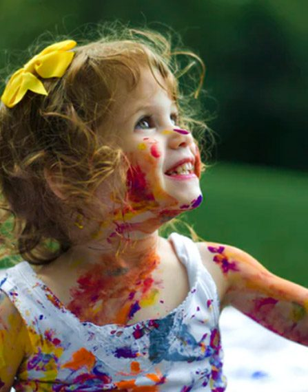 smiling young girl with bright colored paint on her face and clothes