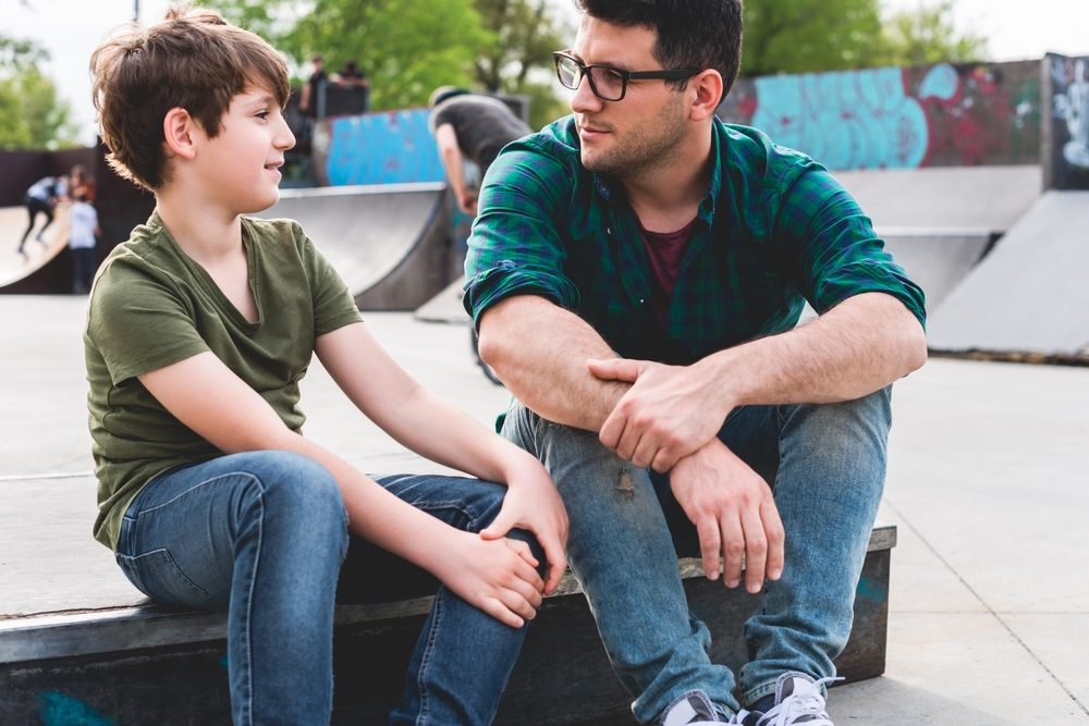 photo of man and teen boy sitting and talking